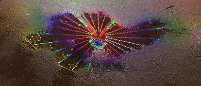 Ein bunt leuchtendes Riesenrad spiegelt sich in einer Pfütze.