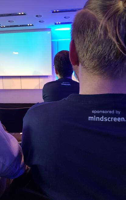 Zwei Teilnehmer der Neos Konferenz mit Konferenz-T-Shirts auf denen das Logo des T-Shirt-Sponsors mindscreen gedruckt ist.